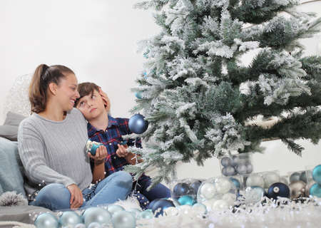 merry christmas and happy holidays! sister and brother decorate the christmas tree. accidentally the child breaks the balls, disconsolately looks at his sister