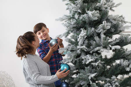 merry christmas family at home, smiling brother and sister decorate the tree hang blue balls