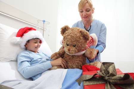 Happy child lying in bed in hospital room with Santa Claus hat and nurse dressing a teddy bear during Christmas holiday