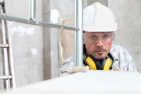 man work, professional construction worker with scaffolding, safety hard hat, hearing protection headphones, gloves and protective glasses. on interior building site background
