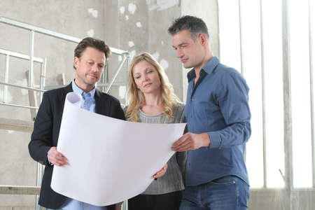 Architect showing house design plans to a young couple. House building goal concept. Meeting at interior construction site to talk about house appearance, interior decoration and home layout