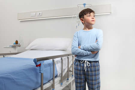 Child in hospital room standing next to bed wearing a pajama isolated on white wall with copy space