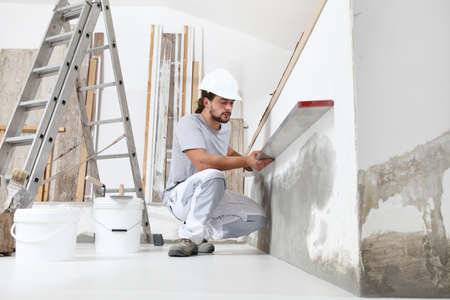 construction worker plasterer man looks at the spirit level and checks the wall in building site of home renovation with tools and building materials on the floor