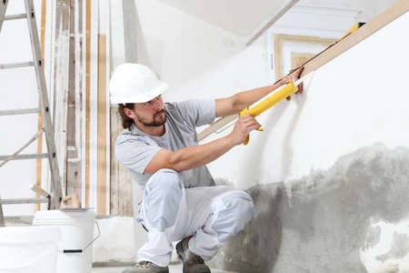construction worker plasterer man uses caulking gun in building site of home renovation with tools and building materials on the floor Stock Photo