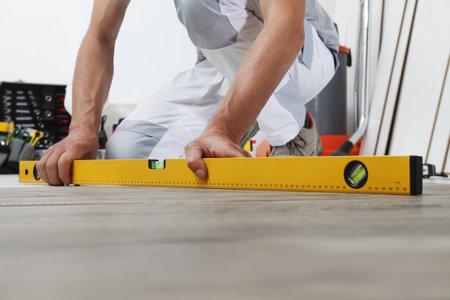 man worker hands installing timber laminate floor. Precise finishing using spirit level. Wooden floors house renovation. Stock Photo