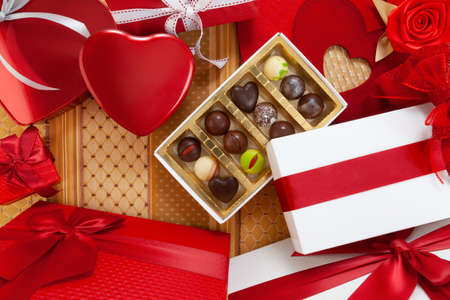Valentines day background, composition of gift boxes chocolates and red heart metal shaped boxes, with bows and ribbons, top view on ornamental fabric. For greeting card or pastry poster template