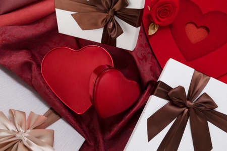 Valentines day background, composition of gift boxes and red heart metal shaped boxes, with bows and ribbons, top view on damask fabric. Useful for greeting card or poster template Reklamní fotografie