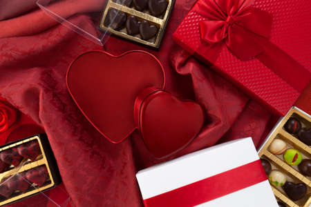 Valentines day background, composition of gift boxes chocolates and red heart metal shaped boxes, with bows and ribbons, top view on damask fabric. Useful for greeting card or pastry poster template