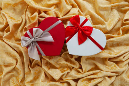 Valentine day, red heart shaped packaging with ribbon bow isolated on damask golden fabric. Useful for greeting gift card Reklamní fotografie