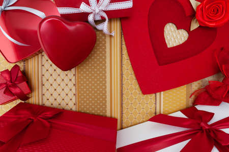 Valentines day background, composition of gift boxes and red heart metal shaped packages, with bows and ribbons, top view on fabric. Useful for greeting card or poster template with copy space