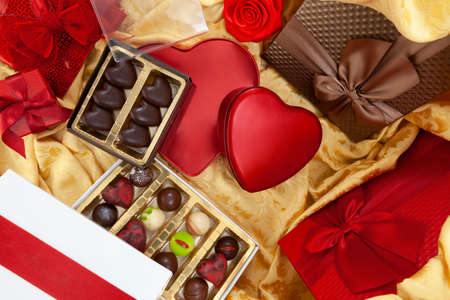 Valentines day background, composition of gift packages chocolates and red heart metal shaped boxes, with bows and ribbons, top view on golden fabric. For greeting card or pastry poster template