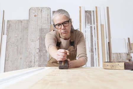 wood crafts, woman artisan carpenter works wood with old handle planer tool in her workshop, restoration, diy and handmade works concept