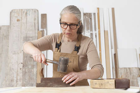 wood crafts, woman artisan carpenter works wood with old handle planer and hammer tools in her workshop, restoration, diy and handmade works concept