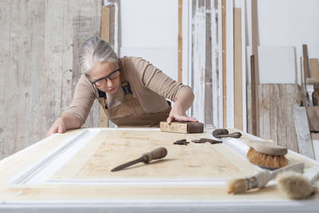 wood crafts, woman artisan carpenter works wood, sand an old door with sandpaper, with old handle tools in her workshop, restoration, diy and handmade works concept Reklamní fotografie