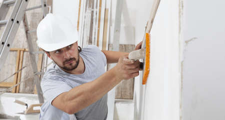 Construction worker are using sponge and plastering trowel to smooth the walls. Home improvement, hands plasterer man at work in interior construction house site and wear helmet, close up