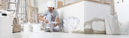 plasterer man at work, take the mortar from the bucket with trowel to plastering the wall of interior construction house site and wear helmet, panoramic image Reklamní fotografie