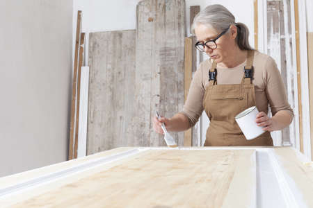 wood crafts, woman artisan carpenter painting with brush and paint jar white the door in workshop, wearing overall and eyeglasses, interior designer, restoration, diy and handmade works concept