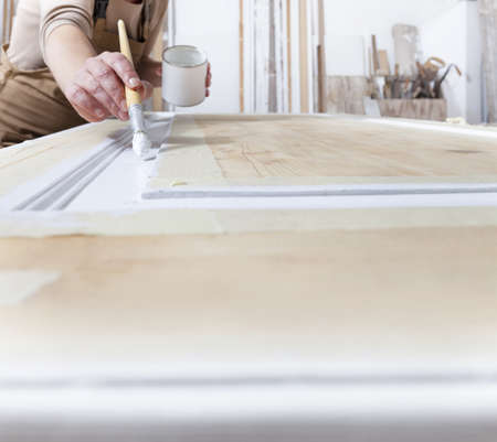wood crafts, close up hands woman artisan carpenter painting with brush and paint jar white the door in workshop, wearing overall, interior designer, restoration, diy and handmade works concept