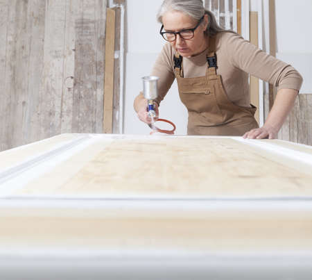 wood crafts, woman artisan carpenter painting with spray gun paint white the door in her workshop, wearing overall and eyeglasses, interior designer, restoration, diy and handmade works concept Reklamní fotografie