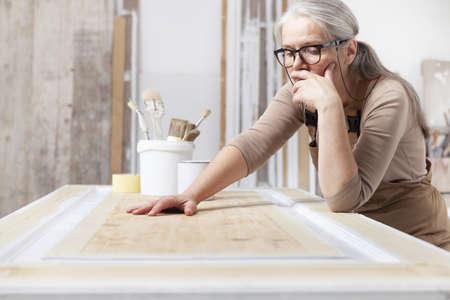 wood crafts, woman artisan carpenter in workshop, wearing overall and eyeglasses, think, check and plan the work, interior designer, restoration, diy and handmade works concept Reklamní fotografie