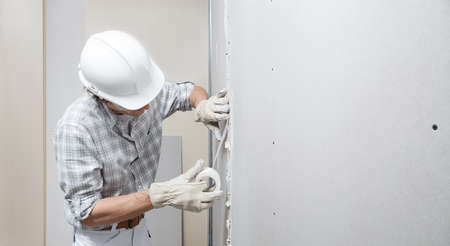 man drywall worker or plasterer putting mesh tape for plasterboard on a wall using a spatula and plaster. Wearing white hardhat, work gloves and safety glasses. Image with copy space
