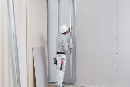 man worker with drywall metal profiles for installing plasterboard sheet to wall. Wearing white hardhat, work gloves and safety glasses. Isolated on white background with copy space