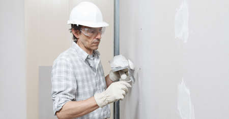 man drywall worker or plasterer putting plaster on plasterboard wall using a trowel and a spatula, fill the screw holes, wearing white hardhat, work gloves and safety glasses.