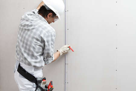 Back view of male drywall worker or plasterer taking measures with meter and pencil, isolated on plasterboard white wall. Wearing hardhat, panoramic image with copy space. Reklamní fotografie