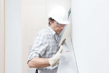 Man drywall worker or plasterer checking level of white plasterboard wall with bubble level at construction site. Wearing white hardhat, work gloves and safety glasses. Close-up portrait. Reklamní fotografie