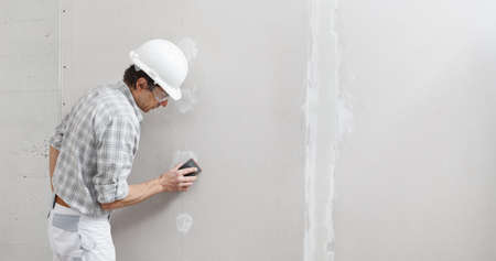 man drywall worker or plasterer sanding and smoothing a plasterboard walls with stucco using a sandpaper holder. Wearing white hardhat and safety glasses. Panoramic image with copy space