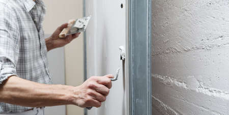 closeup hands man drywall worker or plasterer putting stucco on plasterboard wall using a trowel and a spatula, fill the screw holes