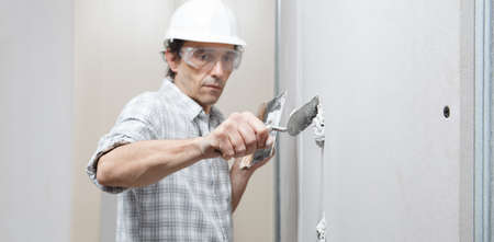 man drywall worker or plasterer putting plaster on plasterboard wall using a trowel and a spatula, fill the screw holes, wearing white hardhat and safety glasses. Reklamní fotografie