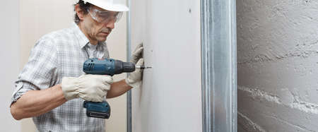 man drywall worker or plasterer using cordless electric screwdriver to fix the plasterboard sheets to the metal profiles to build the new wall. Wearing white hardhat, work gloves and safety glasses