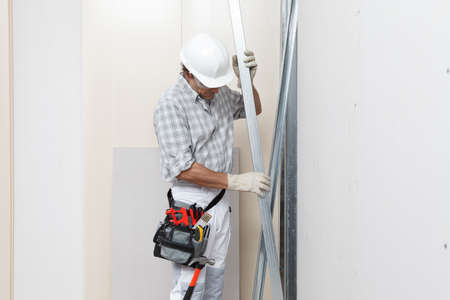 Man construction worker or plasterer holding drywall metal profiles near plasterboard white wall in building site. Wearing white hardhat, work gloves, safety glasses and tool belt.