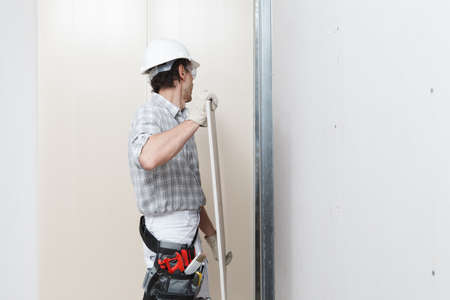 man drywall worker installing plasterboard sheet to wall. Wearing hardhat, work gloves, safety glasses and tool belt. Isolated on white background with copy space