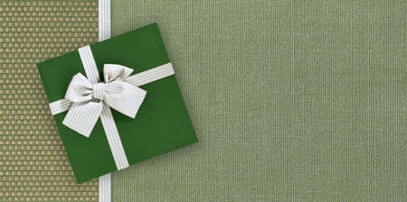Gift card with gift box with ribbon and bow isolated on elegant green fabrics background, top view and copy space template, layout useful for best wishes and shopping concept