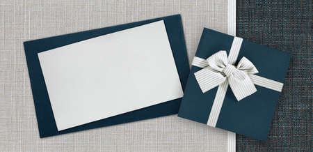 Gift card and gift box with ribbon and bow isolated on elegant blue and gray fabrics background, top view and copy space template, useful for father's day greetin Reklamní fotografie