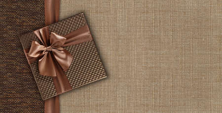 Gift card with gift box with ribbon and bow isolated on elegant brown fabrics background, top view and copy space template, layout useful for best wishes and shopping concept Reklamní fotografie