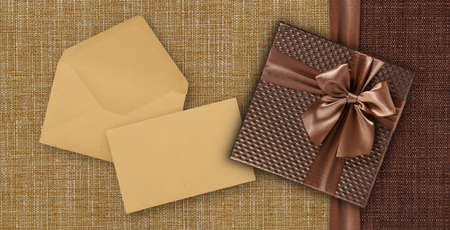 Gift card with gift box with ribbon and bow, envelope and ticket, isolated on elegant brown fabrics background, top view and copy space template, layout useful for best wishes and shopping concept