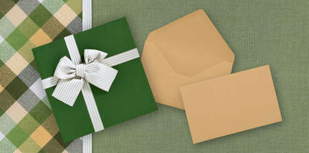 Gift card with gift box with ribbon and bow, envelope and ticket, isolated on elegant green fabrics background, top view and copy space template, layout useful for best wishes and shopping concept