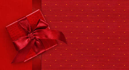 Gift card with gift box with ribbon and bow, isolated on elegant red fabrics background, top view and copy space template, layout useful for best Christmas wishes or valentine shopping concept
