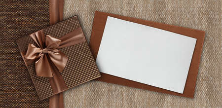 Gift card with gift box with ribbon and bow, isolated on elegant brown fabrics background, top view and copy space template, layout useful for best wishes and shopping concept Reklamní fotografie