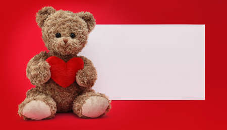 gift card, funny teddy bear with red heart isolated on red background, white sign template with copy space