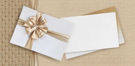 Gift card, gift box with beige ribbon bow isolated on elegant pearly fabrics background, top view and copy space template, layout useful for best wishes and shopping concept Reklamní fotografie