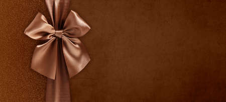 gift card with bright and shiny ribbon bow isolated on brown grunge background, top view and copy space template, layout useful for best wishes and shopping concept