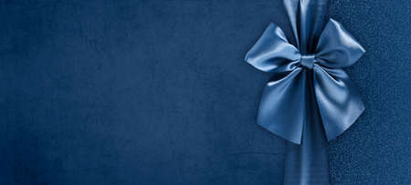 gift card with bright and shiny ribbon bow isolated on blue grunge background, top view and copy space template, layout useful for best wishes and shopping concept Reklamní fotografie