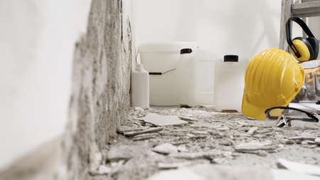 house renovation concept, wall in demolition with plaster rubble and protective construction work tools, paints, primer, buckets and jerry cans of building products, white background with copy space