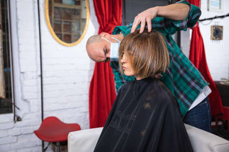 woman being combed by hairdresser with spray and blow dryer in front of mirror in modern retro hair salon