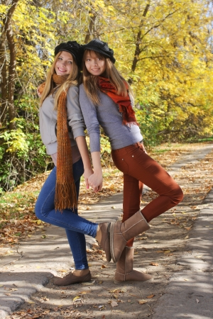 Two funny girls friends having fun in autumn park photo