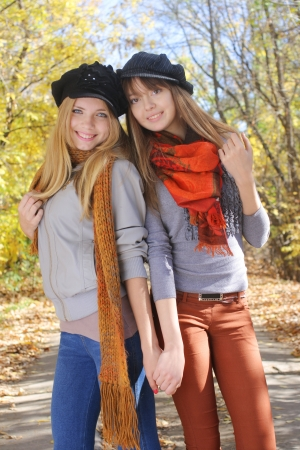 two beautiful teenage girls hugging in the autumn park photo